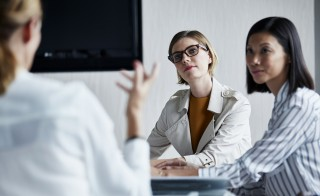 Businesswomen listening to colleague in office