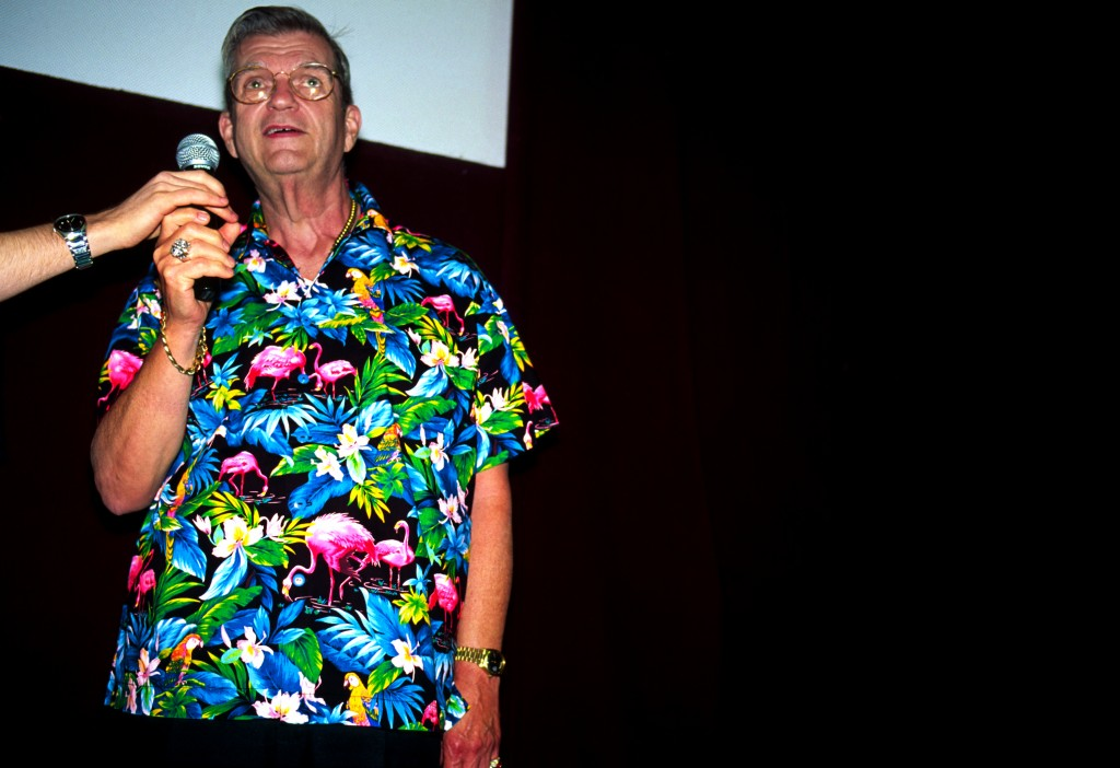 "WEST NEWTON, MA - JUNE 13:  After a screening of a NYU film student's film short ""Plastic Migration"" honoring the plastic pink flamingo, Donald Featherstone, the inventor of the plastic pink flamingo, answers audience questions in his trademark flamingo pattered shirt on June 13, 2004 in West Newton, Massachusetts.  The original plastic pink flamingo was made by Union Products, a plastics manufacturing company in Leominster, Massachusetts after it was invented by Donald Featherstone in 1957.  Citing the rising costs of electricity, plastic resin and financing, the plastic pink flamingo, age 49, met its demise.  Long venerated as an icon of American kitsch, the flamingo was in equal measures reviled and revered.  (Photo by Jeff Hutchens/Getty Images)"