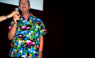 """WEST NEWTON, MA - JUNE 13:  After a screening of a NYU film student's film short """"Plastic Migration"""" honoring the plastic pink flamingo, Donald Featherstone, the inventor of the plastic pink flamingo, answers audience questions in his trademark flamingo pattered shirt on June 13, 2004 in West Newton, Massachusetts.  The original plastic pink flamingo was made by Union Products, a plastics manufacturing company in Leominster, Massachusetts after it was invented by Donald Featherstone in 1957.  Citing the rising costs of electricity, plastic resin and financing, the plastic pink flamingo, age 49, met its demise.  Long venerated as an icon of American kitsch, the flamingo was in equal measures reviled and revered.  (Photo by Jeff Hutchens/Getty Images)"""