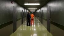 Photo of prison guard with prisoner by Halfdark via Getty Images