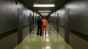 Photo of prison guard with prisoner by Halfdark via Getty Images