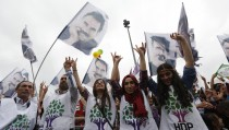 Supporters of the Pro-Kurdish Peoples' Democratic Party (HDP) cheer next to flags with a picture the jailed Kurdish militant leader Abdullah Ocalan during a gathering to celebrate their party's victory during the parliamentary election, in Istanbul, Turkey, June 8, 2015. Turkey faced the prospect of weeks of political turmoil after the ruling AK Party lost its parliamentary majority in weekend polls, dealing a blow to President Tayyip Erdogan's ambitions to acquire sweeping new powers.  REUTERS/Murad Sezer  - RTX1FO7L