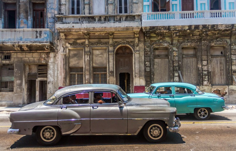 "Old cars pass buildings falling apart near the Malecon in Havana. Cuba is truly a place ""frozen in time."" Photo by Frank Carlson"