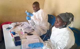 Health worker prep the Ebola vaccine in Guinea's capital, Conakry. Here, the outbreak continues with two new cases of Ebola being reported last week in the nation's largest city. Photo by Caleb Hellerman.