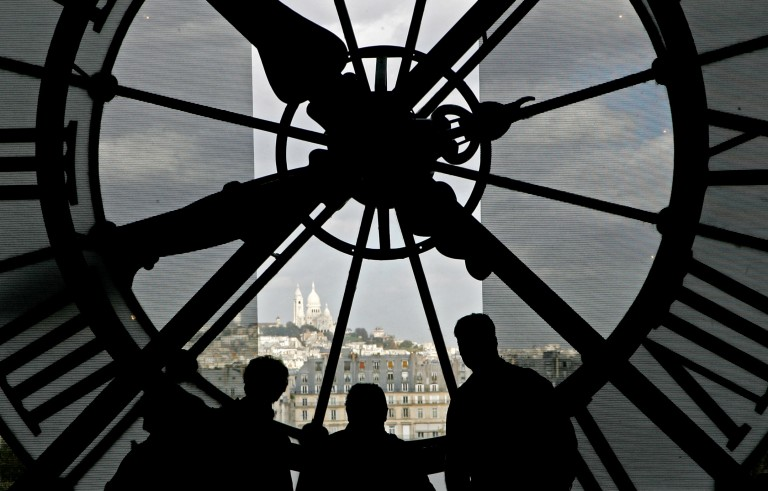 Visitors look out through the glass clock face at the Musee d'Orsay towards the Sacre Coeur in Paris November 3, 2005. Photo by Toby Melville/Reuters