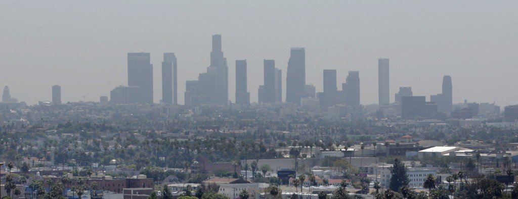The skyline of downtown Los Angeles through a layer of smog is seen in the distance from a rooftop in Hollywood, California. Photo by REUTERS/Fred Prouser/Files