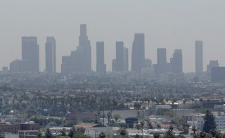The skyline of downtown Los Angeles through a layer of smog is seen in the distance from a rooftop in Hollywood, California, May 31, 2006. U.S. environmental regulators proposed on January 7, 2010 stronger standards on lung and heart disease-causing smog that could cost industry up to $90 billion to implement. REUTERS/Fred Prouser/Files   (UNITED STATES - Tags: ENVIRONMENT BUSINESS) - RTR28N0R