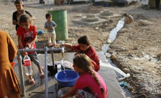 Displaced Iraqis, who escaped the Islamic State violence in Mosul, collected water at Baharka refugee camp in Erbil in the Kurdish region on Sept. 14, 2014. Photo by Ahmed Jadallah/Reuters