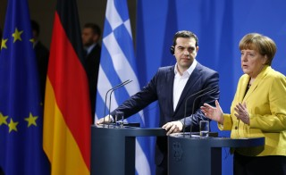 German Chancellor Angela Merkel and Greek Prime Minister Alexis Tsipras address a news conference. Tsipras is pressing for cash to keep his country afloat. Photo by REUTERS/Hannibal Hanschke    - RTR4UJAA