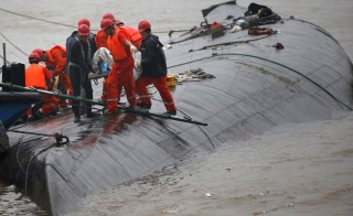 Rescue workers carry a body from a sunken ship in the Yangtze River. Photo by Kim Kyung-Hoon/Reuters