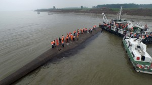 An aerial view shows rescue workers searching on the sunken ship at Jianli section of Yangtze River, Hubei province, China, June 2, 2015. Rescuers fought bad weather on Tuesday as they searched for more than 400 people, many of them elderly Chinese tourists, missing after a cruise boat was buffeted by a freak tornado and capsized on the Yangtze River. REUTERS/Stringer CHINA OUT. NO COMMERCIAL OR EDITORIAL SALES IN CHINA - RTR4YHPC