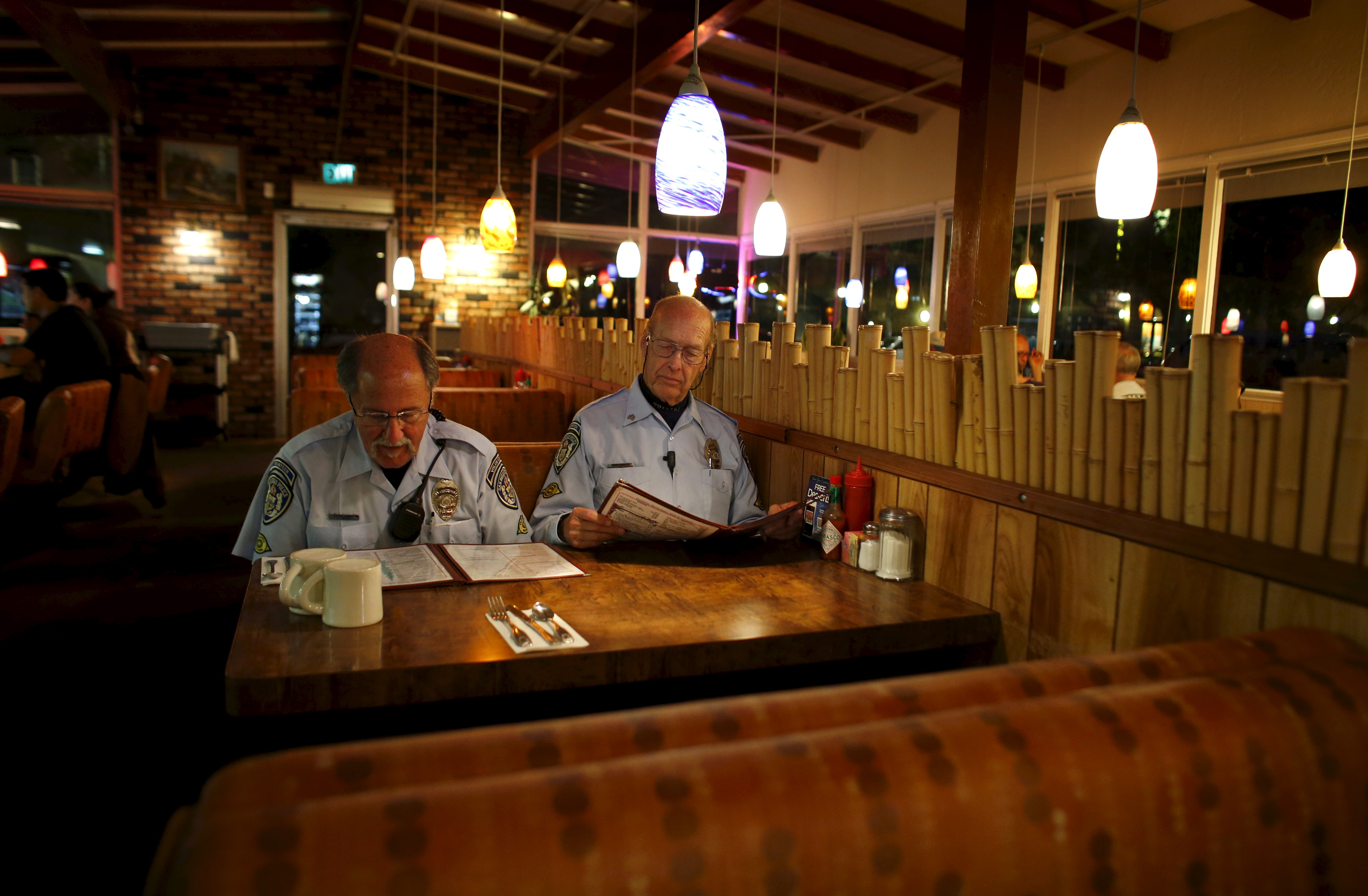 Retired Senior Volunteer Patrol member Steve Rubin (L) and Henry Miller grab a late meal at a restaurant while out on patrol, March 10, 2015. Photo by Mike Blake/Reuters