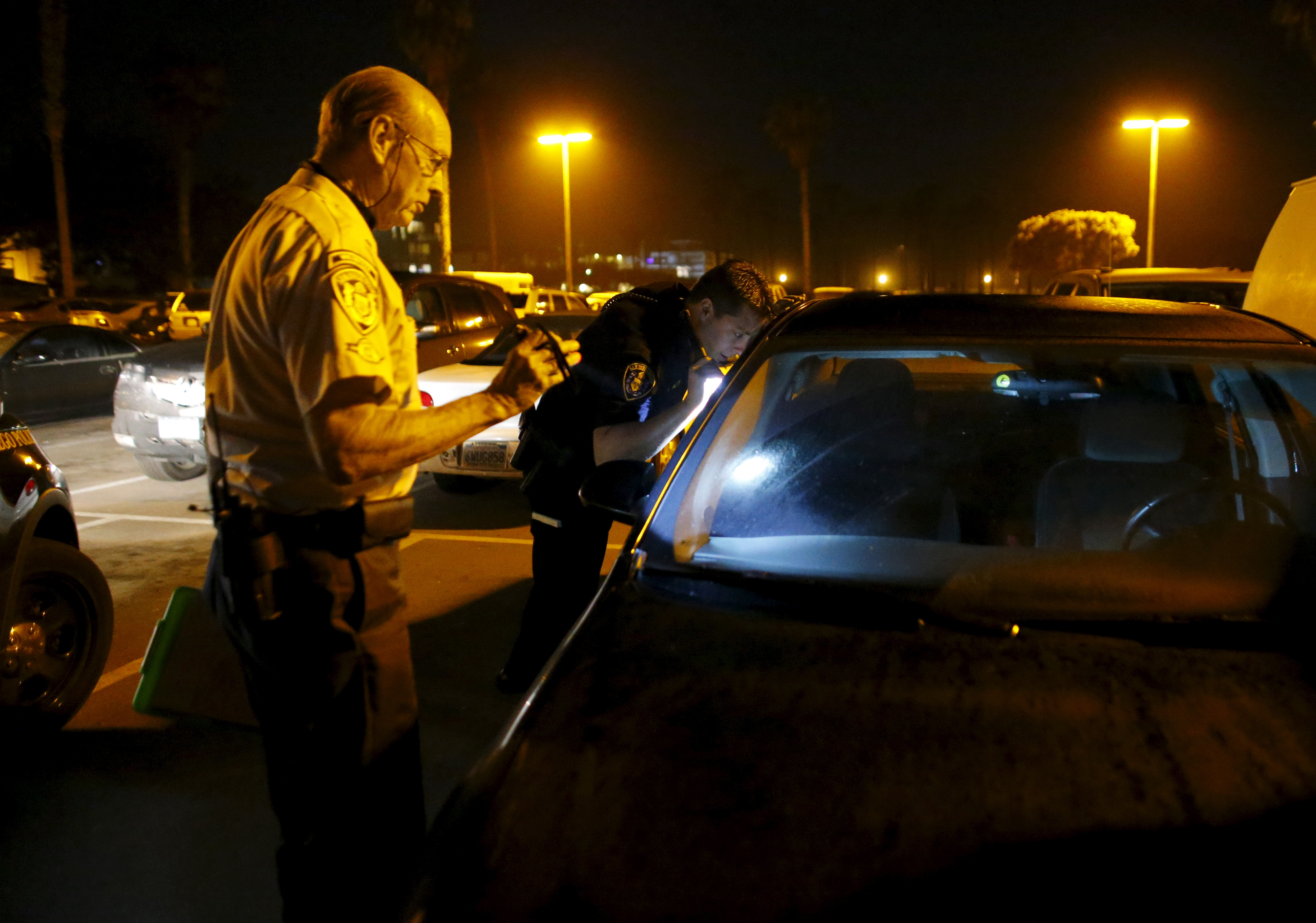 RSVP member Henry Miller (L) is assisted by San Diego Police officer Joe Hilton after Miller found a stolen vehicle on his night patrol with partner Steve Rubin in San Diego, California on April 30, 2015. Photo by Mike Blake/Reuters