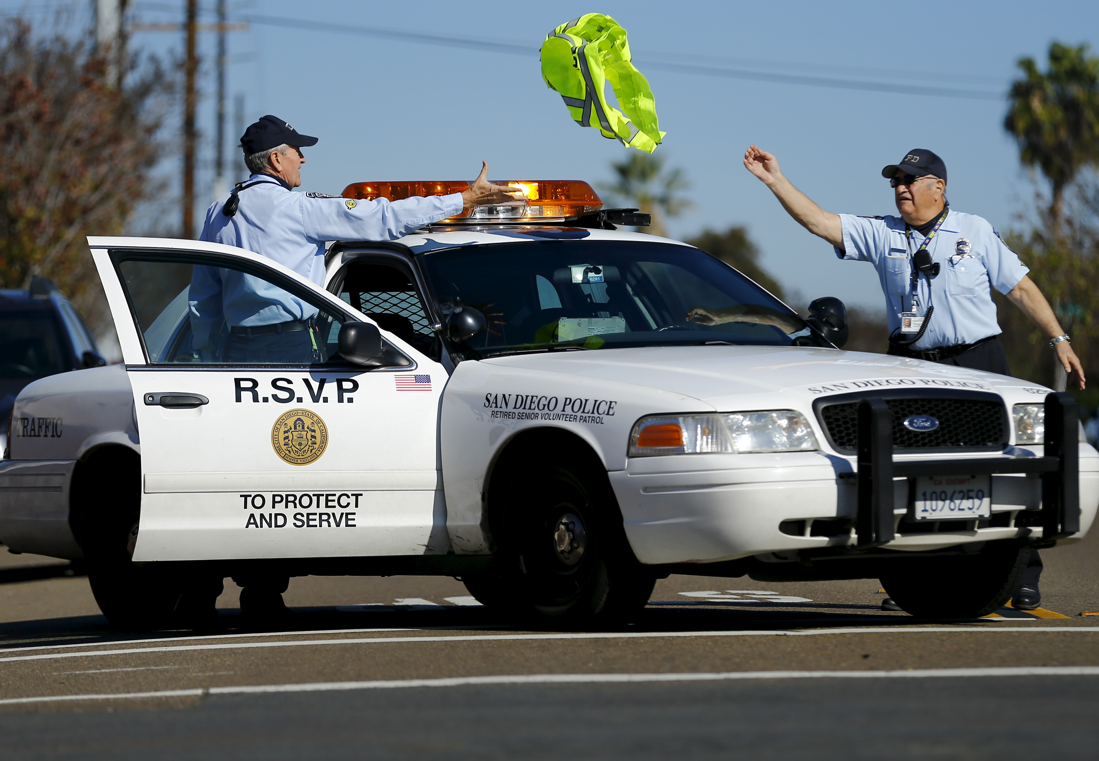 88-year-old Ed Robles (R) throws a safety vest to partner Dick Engel after directing traffic at the scene of a car accident, February 4, 2015. Photo by Mike Blake/Reuters