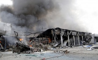 A firefighter works to extinguish a fire at a local market, which was recently damaged by shelling, in Donetsk, Ukraine, June 3, 2015. Ukrainian troops and pro-Russian separatists on Wednesday fought their first serious battles in months and Ukraine's defense minister said an attempt by rebels to take the eastern town of Maryinka had been thwarted. Ukraine's military said the Russian-backed rebels had tried to advance using tanks and up to 1,000 fighters west of the main rebel stronghold of Donetsk, in the most significant escalation of the conflict in around three months and in defiance of a ceasefire deal. REUTERS/Alexander Ermochenko - RTR4YOCJ