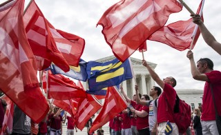 Supporters of gay marriage rally in front of the Supreme Court in Washington June 25, 2015. A decision in Obergefell v. Hodges, a test of a constitutional right to same-sex marriage, is expected in the coming days.  REUTERS/Joshua Roberts - RTR4YXV2