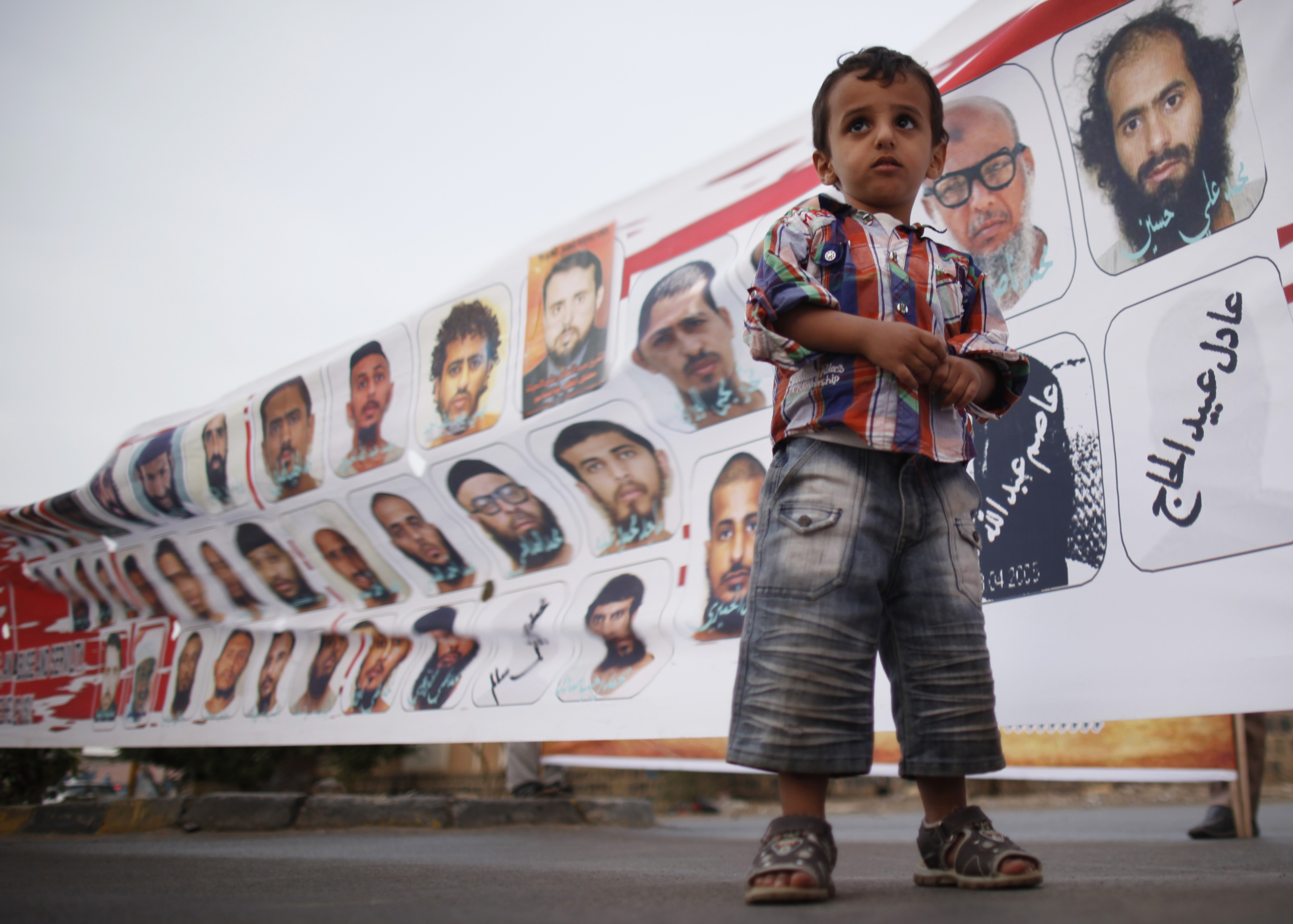 A boy stands outside the U.S. embassy in Sanaa in front of pictures depicting Yemeni detainees at Guantanamo Bay prison during a protest demanding the release of the detainees on July 21, 2013. Six Yemenis will be transferred to Oman today from Guantanamo, continuing President Obama's campaign to close the prison. Photo by Khaled Abdullah Ali Al Mahd/Reuters