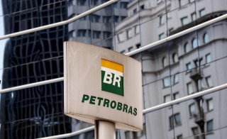 The Petrobras logo is seen in front of the company's headquarters in Sao Paulo April 23, 2015. Executives at Brazil's Petrobras on Thursday sought to move on from a giant corruption scandal that has plagued the state-run oil company, outlining a back-to-basics recovery plan that left some investors hoping the worst was over. On a call with investors the day after publishing long-delayed audited results for 2014, Chief Financial Officer Ivan Monteiro said the focus was on reducing debt, selling non-core assets and continuing to increase oil production through careful investments in high-return assets. Photo by Paulo Whitaker/Reuters