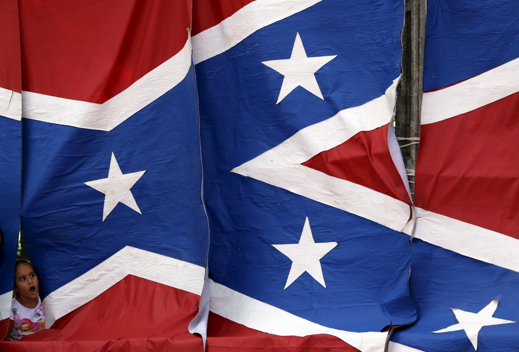 A descendant of American Southerners looks through the Confederate flag during a party to celebrate the 150th anniversary of the end of the Civil War, Santa Barbara D'Oeste, Brazil, April 26, 2015. The flag has become the subject of controversy following Wednesday's racially-motivated mass shooting in Charleston, South Carolina. Photo by Paulo Whitaker/Reuters