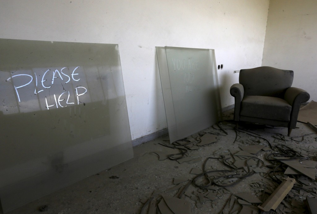 """Please help,"" reads graffiti inside a manager's office at a deserted textile factory that closed in 1995 near the town of Larissa in Thessaly region, Greece April 22, 2015. Photo by Yannis Behrakis/Reuters"