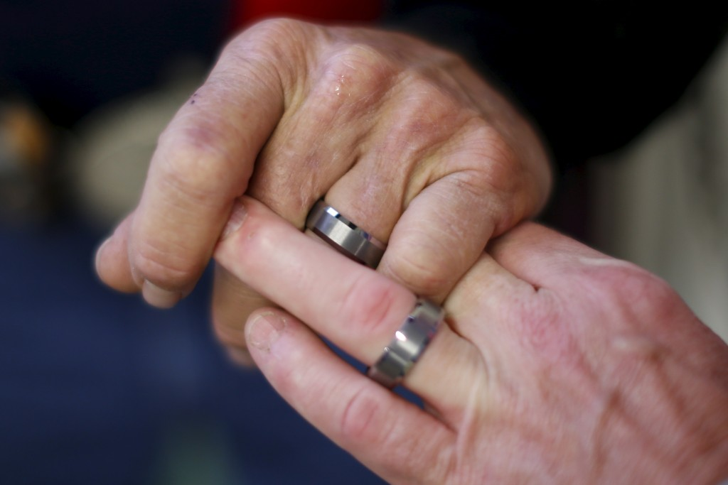 Gordon Satterly, 61, from Michigan holds hands with his husband Richard Brand, 53, from Texas, at the International Gay Rodeo Association's Rodeo In the Rock party. Photo by Lucy Nicholson/Reuters