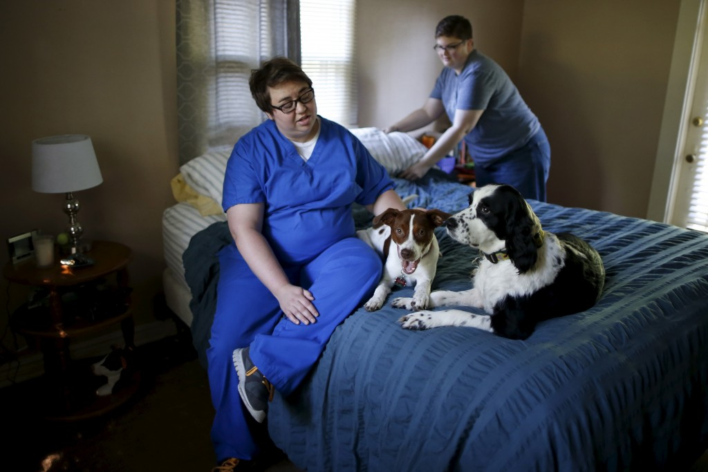 Ashley Vickers, 29, (L) and her fiancee Sara Strickland, 32, play with their two dogs as they get ready for breakfast at their home in Little Rock, Arkansas, April 29, 2015. Photo by Lucy Nicholson/Reuters