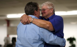 U.S. Marine veteran Sandy Bidwell, 68 and her wife, former Army National Guard veteran, Lisa Smith, 59, embrace. An estimated 780,000 Americans are in a same-sex marriage, accoridng to an April poll. Photo by Lucy Nicholson/Reuters