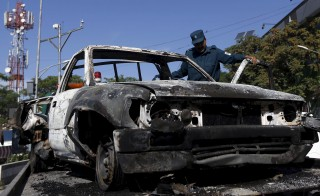 An Afghan policeman inspects the wreckage of a car after a Taliban attack on a guesthouse in Kabul May 27, 2015. Four Taliban insurgents armed with assault rifles and a grenade launcher stormed a guesthouse in the diplomatic quarter of the Afghan capital overnight and held out for hours until they were killed by government forces early on Wednesday, officials said.  REUTERS/Omar Sobhani    - RTX1EOEF