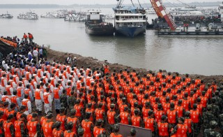 Rescue workers hold a moment of silence at a ceremony to mark the seventh day since the Eastern Star went down in the Jianli section of Yangtze River, Hubei province, China, June 7, 2015. The death toll from a Chinese cruise ship which capsized during a storm in the Yangtze River reached 406 on Sunday, leaving fewer than 40 still missing, as officials and rescuers bowed in mourning towards the battered boat. Sunday marks seven days since the Eastern Star went down, and according to Chinese tradition this a key date on which to mourn the dead. REUTERS/Kim Kyung-Hoon       TPX IMAGES OF THE DAY      - RTX1FG65