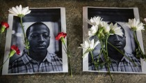 Flowers rest on top of pictures of Kalief Browder in New York June 11, 2015. New York City Mayor Bill de Blasio on Monday vowed to push reforms at the city's troubled Rikers Island prison complex after the reported weekend suicide of the 22-year-old Browder who had been held there for three years without being convicted of a crime. REUTERS/Lucas Jackson  - RTX1G64W