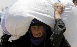 A Syrian refugee carries her belongings in Sanliurfa province, Turkey on June 17. Photo by Umit Bektas/Reuters