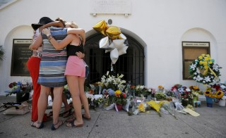 Mourners hug after praying outside the Emanuel African Methodist Episcopal Church in Charleston, South Carolina June 18, 2015, a day after a mass shooting left nine dead during a bible study at the church.  REUTERS/Brian Snyder - RTX1H60G