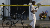 Larry Gorham rode his bicycle to pay his respects outside the Emanuel African Methodist Episcopal Church in Charleston, South Carolina June 19, 2015, two days after a mass shooting left nine dead during a bible study at the church. REUTERS/Brian Snyder - RTX1H94D