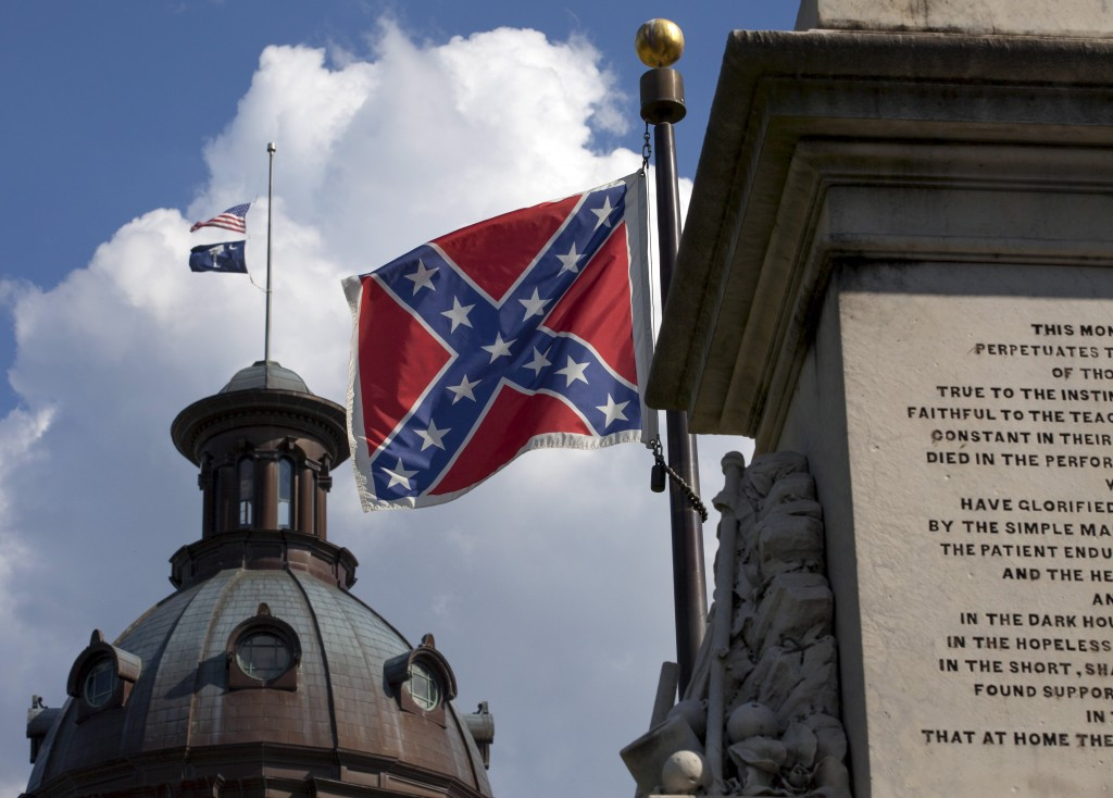 The U.S. flag and South Carolina state flag flies at half staff to honor the nine people killed in the Charleston murders as the confederate battle flag also flies on the grounds of the South Carolina State House in Columbia, SC June 20, 2015. REUTERS/Jason Miczek - RTX1HF3B