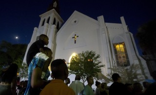 A father carries his son as they listen to gospel music during a vigil outside Emanuel African Methodist Episcopal Church in Charleston, June 20, 2015. Today, mourners are gathering to remember the church's pastor the Rev. Clementa Pinckney. Photo by Carlo Allegri/Reuters