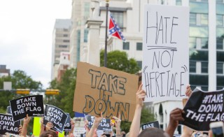 "People hold signs during a protest asking for the removal of the confederate battle flag that flies at the South Carolina State House in Columbia, South Carolina on June 20, 2015. Republican Mike Huckabee believes a potential president cannot ""weigh in on every little issue in all 50 states."" Photo by Jason Miczek/Reuters"
