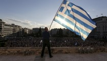 A man waves a Greek national flag while standing at the premises of the parliament building during a rally in front of the parliament building calling on the government to clinch a deal with its international creditors and secure Greece's future in the Eurozone, in Athens, Greece, June 22, 2015. Euro zone finance ministers welcomed new Greek proposals for a cash-for-reform deal on Monday but said they required detailed study and it would take several days to determine whether they can lead to an agreement to avert a default. REUTERS/Yiannis Liakos/Intimenews  GREECE OUT. NO COMMERCIAL OR EDITORIAL SALES IN GREECE - RTX1HN8D