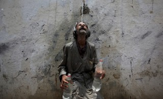 A man cools off under a public tap during a heat wave in Karachi, Pakistan on June 23. Hundreds have died in the southern city over the past several days, health officials said, as paramilitaries set up emergency medical camps in the streets. Photo by Akhtar Soomro/Reuters