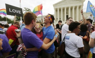 Gay rights supporters celebrate after the U.S. Supreme Court ruled that the U.S. Constitution provides same-sex couples the right to marry, outside the Supreme Court building in Washington, June 26, 2015. Photo by REUTERS/Jim Bourg - RTX1HXGA