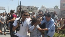Police officers control the crowd (rear) while surrounding a man (front C) suspected to be involved in opening fire on a beachside hotel in Sousse, Tunisia, as a woman reacts(R), June 26, 2015. At least 27 people, including foreign tourists, were killed when at least one gunman opened fire on a Tunisian beachside hotel in the popular resort of Sousse on Friday, an interior ministry spokesman said. Police were still clearing the area around the Imperial Marhaba hotel and the body of one gunman lay at the scene with a Kalashnikov assault rifle after he was shot in an exchange of gunfire, a security source at the scene said. REUTERS/Amine Ben Aziza   TPX IMAGES OF THE DAY      - RTX1HXGI
