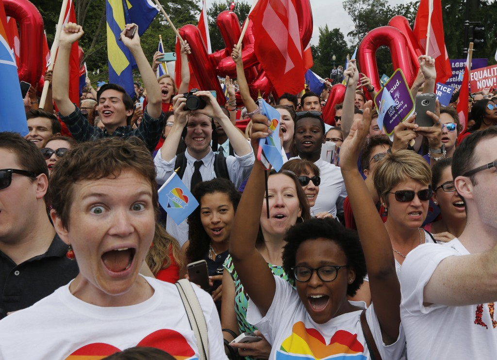 Gay rights supporters celebrate after the U.S. Supreme Court ruled that the U.S. Constitution provides same-sex couples the right to marry, outside the Supreme Court building in Washington, June 26, 2015. REUTERS/Jim Bourg - RTX1HXN9