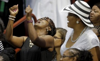 Mourners sing along with the choir ahead of funeral services for the Reverend Clementa Pinckney in Charleston, South Carolina June 26, 2015. Pinckney is one of the nine victims of the mass shooting at the Emanuel African Methodist Episcopal Church.  REUTERS/Brian Snyder - RTX1HXPE
