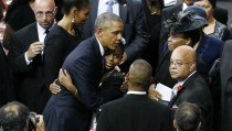 U.S. President Barack Obama hugs Rev. Clementa Pinckney's daughter Eliana as her mother Jennifer (R) looks on after the president eulogized Rev. Pinckney during funeral services in Charleston, South Carolina June 26, 2015. Pinckney was among the nine people who died when a gunman opened fire in the mass shooting during bible study at Emanuel African Methodist Episcopal Church. REUTERS/Jonathan Ernst  - RTX1HZHF