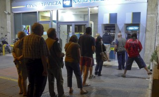 "People line up at an ATM outside a National Bank branch in Athens, Greece early June 27, 2015.  Greek Prime Minister Alexis Tsipras called a referendum on bailout demands from foreign creditors on Saturday, rejecting an ""ultimatum"" from lenders and putting a deal that could determine Greece's future in Europe to a risky popular vote. Photo by Yiannis Panagopoulos/Eurokinissi/Reuters"