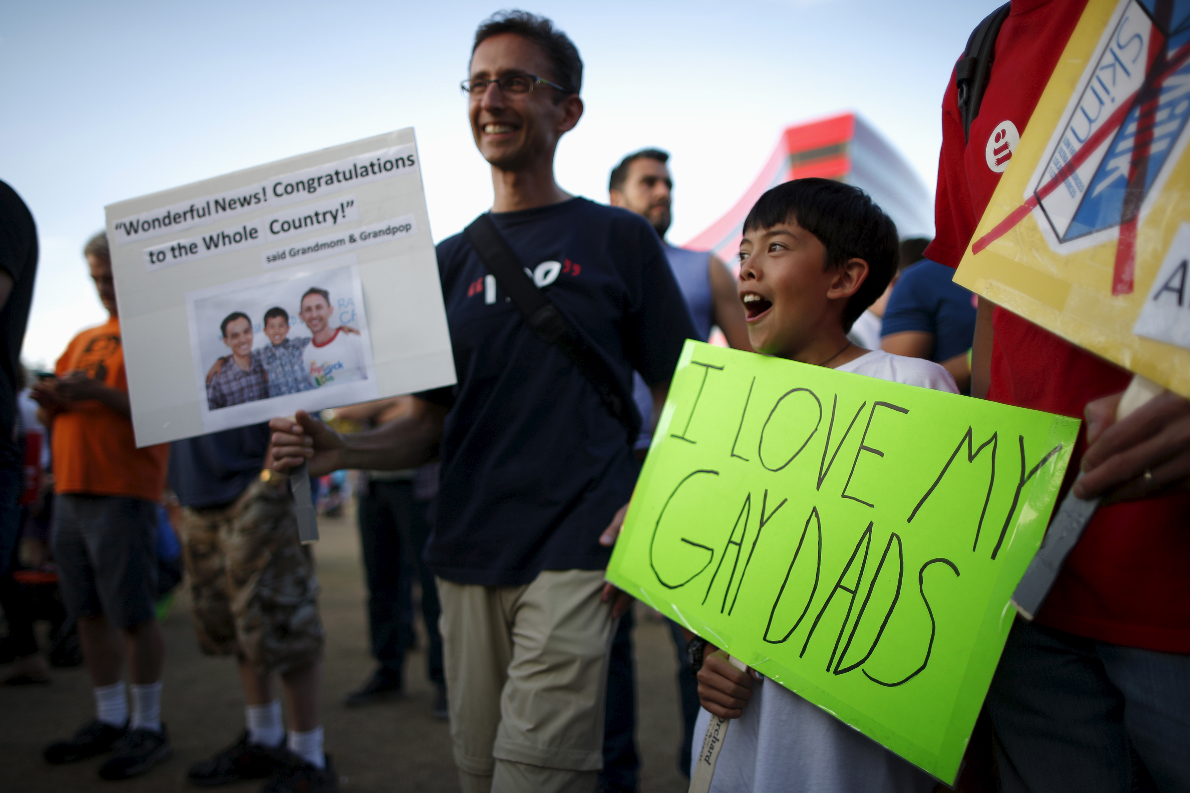 Aaron Ky-Riesenbach, 12, (R) carries a sign as he stands with his father Larry Riesenbach, 55, at a celebration rally in West Hollywood, California, United States, June 26, 2015. The U.S. Supreme Court ruled on Friday that the U.S. Constitution provides same-sex couples the right to marry in a historic triumph for the American gay rights movement. REUTERS/Lucy Nicholson - RTX1I0I0