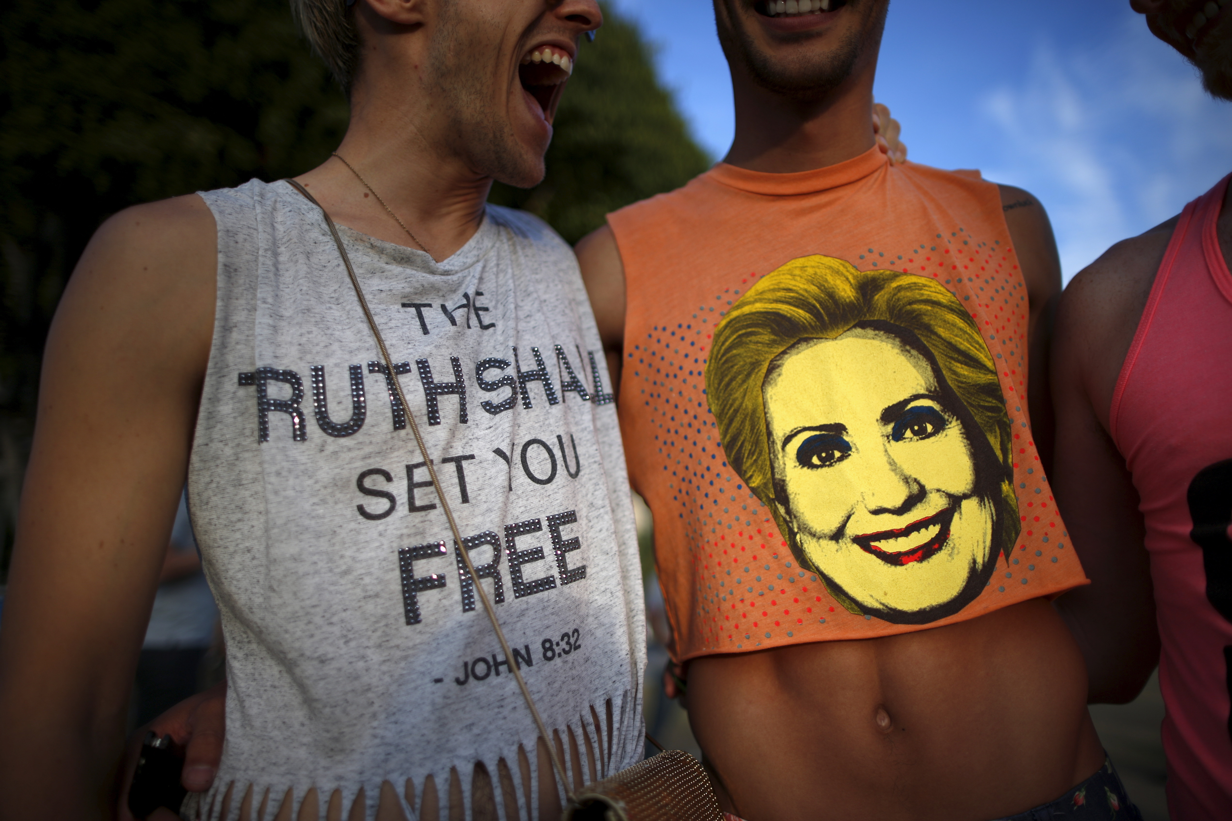 "A man wears a shirt saying ""The Ruth Shall Set You Free,"" a reference to U.S. Supreme Court Justice Ruth Bader Ginsburg, as he stands next to a man with a Hillary Clinton shirt at a celebration rally in West Hollywood, California, United States, June 26, 2015. The U.S. Supreme Court ruled on Friday that the U.S. Constitution provides same-sex couples the right to marry in a historic triumph for the American gay rights movement. REUTERS/Lucy Nicholson - RTX1I0JG"