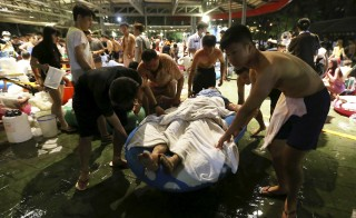 People carry an injured victim from an accidental explosion during a music concert at the Formosa Water Park in New Taipei City, Taiwan, June 27, 2015. About 200 people were injured after a fire suspected to have stemmed from the explosion of an unknown flammable powder occurred in a recreational park in northern Taiwan, local media reported on Saturday. REUTERS/Wu Chia  TAIWAN OUT. NO COMMERCIAL OR EDITORIAL SALES IN TAIWAN - RTX1I2DN