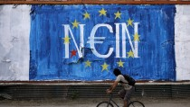 "A man cycles by fresh anti-EU graffiti in Athens, Greece June 28, 2015. Greece said it may impose capital controls and keep its banks shut on Monday after creditors refused to extend the country's bailout and savers queued to withdraw cash, taking Athens' standoff with the European Union and the International Monetary Fund to a dangerous new level. The word painted over the European Union flag reads, ""No"".      REUTERS/Alkis Konstantinidis - RTX1I5AG"