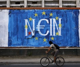 """A man cycles by fresh anti-EU graffiti in Athens, Greece June 28, 2015. Greece said it may impose capital controls and keep its banks shut on Monday after creditors refused to extend the country's bailout and savers queued to withdraw cash, taking Athens' standoff with the European Union and the International Monetary Fund to a dangerous new level. The word painted over the European Union flag reads, """"No"""".      REUTERS/Alkis Konstantinidis - RTX1I5AG"""