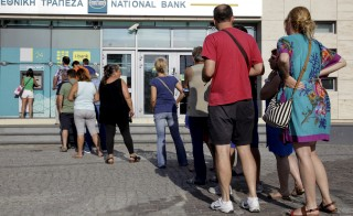 People line up to withdraw cash from an automated teller machine (ATM) outside a National Bank branch in Iraklio on the island of Crete, Greece June 28, 2015. Greece's Prime Minister Alexis Tsipras on Sunday announced a bank holiday and capital controls after Greeks responded to his surprise call for a referendum on bailout terms by pulling money out of banks.  REUTERS/Stefanos Rapanis - RTX1I5SI